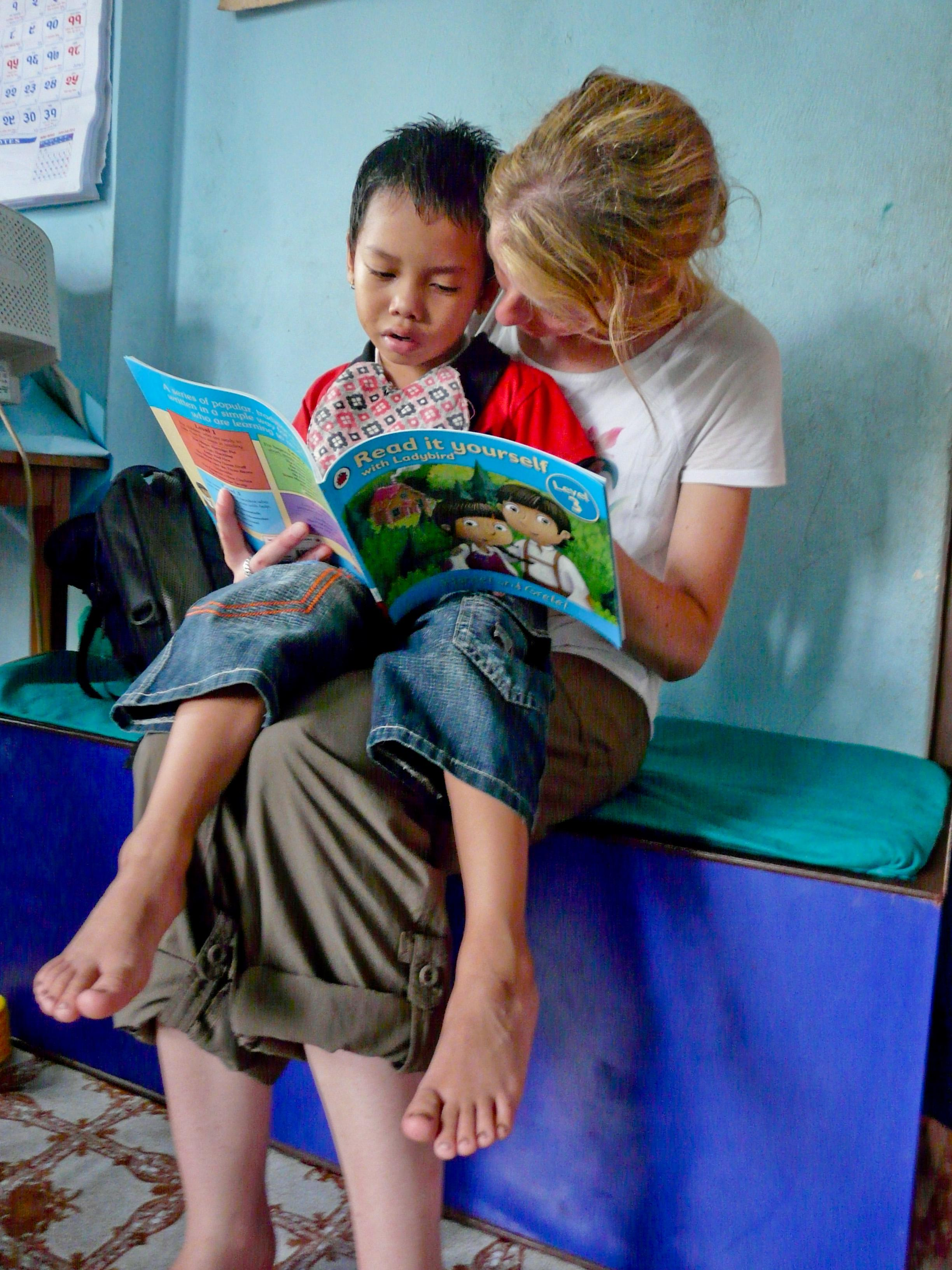 A child and Projects Abroad student read a book on the Physiotherapy internship for teenagers in Nepal.